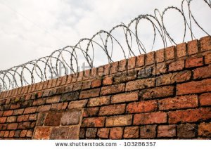 stock-photo-a-barbed-wire-coil-mounted-on-top-of-a-brick-wall-103286357